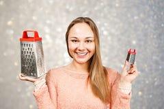 年轻美女画象拿着在灰色闪闪发光背景的磨丝器  库存图片