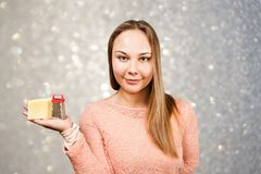年轻美女画象拿着在灰色闪闪发光背景的磨丝器  库存照片