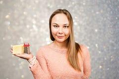 年轻美女画象拿着在灰色闪闪发光背景的磨丝器  免版税图库摄影