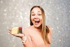 年轻美女画象拿着在灰色闪闪发光背景的磨丝器  免版税库存照片