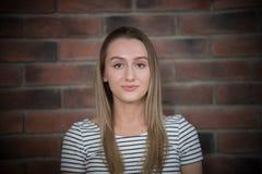 年轻美女画象有长的金发的在砖墙背景 库存照片