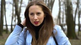 年轻美女站立单独在公园和神色入照相机 她微笑 棕色毛发与长发 ?treadled 股票视频