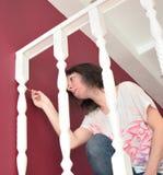 年轻美女绘画壁架ballustrade白色与刷子 免版税图库摄影