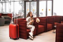 年轻美女读书电话留言在机场休息室 免版税库存照片