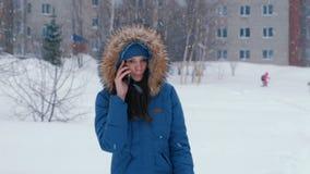 年轻美女谈话在冬天降雪的电话户外 股票视频