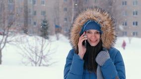 年轻美女谈话在冬天降雪的电话户外 股票录像
