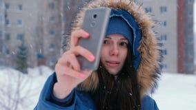 年轻美女谈话在手机的录影在冬天 股票视频