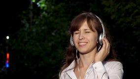 年轻美女跳舞,微笑和享受音乐在晚上在公园在灯笼下光  特写镜头 愉快 股票录像