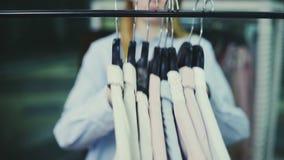 年轻美女采取从挂衣架的所有礼服 股票录像