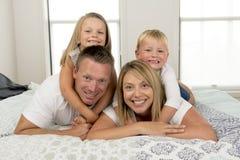 年轻美好和光芒四射的夫妇30到40岁微笑的愉快摆在的甜说谎在与小儿子和美好的daught的床上 免版税库存照片