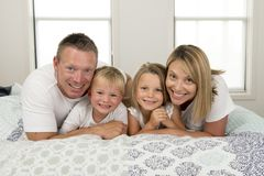 年轻美好和光芒四射的夫妇30到40岁微笑的愉快摆在的甜说谎在与小儿子和美好的daught的床上 库存照片