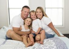 年轻美好和光芒四射的夫妇30到40岁微笑的愉快摆在的甜说谎在与小儿子和美好的daught的床上 库存图片