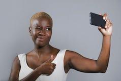年轻美好和愉快黑美国黑人妇女微笑激动的采取selfie与手机的图片画象或记录 库存照片