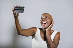 年轻美好和愉快黑美国黑人妇女微笑激动的采取selfie与手机的图片画象或记录 免版税图库摄影