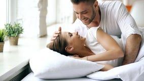 年轻美好和爱恋的夫妇在早晨醒 有吸引力的人亲吻和在床上拥抱他的妻子 库存图片