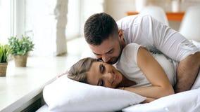 年轻美好和爱恋的夫妇在早晨醒 有吸引力的人亲吻和在床上拥抱他的妻子 免版税库存照片