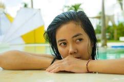 年轻美好和甜亚洲印度尼西亚少年女孩游泳户外画象在热带手段水池微笑的愉快和 库存照片