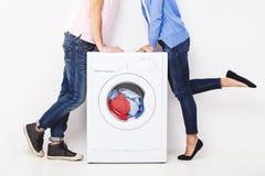 年轻美好的加上一台洗衣机,在白色背景 免版税图库摄影