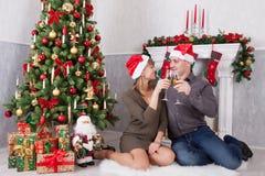年轻美好的加上香槟坐在与xmas礼物的圣诞树附近的一杯 与圣诞节长袜的一个壁炉 免版税库存照片