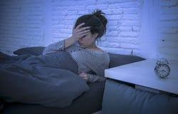 年轻美好的哀伤和担心的拉丁妇女遭受的失眠和无法失眠的问题在晚上说谎的o后睡觉 免版税库存照片