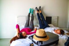 为冒险准备 年轻夫妇为蜜月做准备,说谎在带着旅行手提箱的床上 库存图片