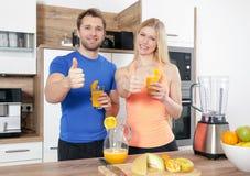 年轻美好的夫妇做一smoothy与搅拌器 免版税库存图片