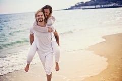 年轻美好的夫妇在度假 在人从上面跳跃的女孩 永远爱 儿童有父亲的乐趣一起使用 库存图片