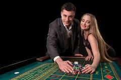 年轻美好的夫妇采取他们的赏金在轮盘赌桌上在赌博娱乐场 库存图片