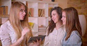年轻美好的女同性恋的夫妇特写镜头射击谈话与与片剂的女性地产商关于购买公寓 影视素材