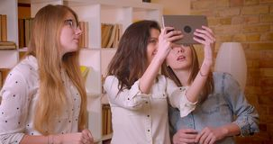 年轻美好的女同性恋的夫妇特写镜头射击谈话与关于购买公寓的女性地产商使用片剂 股票录像