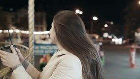 年轻美好的女孩模型在游乐园的晚上 有一杯咖啡的妇女在手上 股票录像