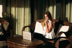年轻美好的女孩用途在一个断裂期间的一台膝上型计算机在工作 夏天 库存图片