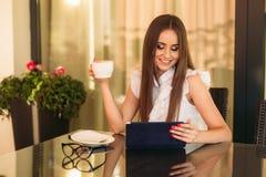 年轻美好的女孩用途在一个断裂期间的一台膝上型计算机在工作 夏天 免版税图库摄影