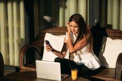年轻美好的女孩用途在一个断裂期间的一台膝上型计算机在工作 蝴蝶日草夏天晴朗的swallowtail 图库摄影