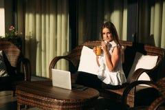 年轻美好的女孩用途在一个断裂期间的一台膝上型计算机在工作 蝴蝶日草夏天晴朗的swallowtail 库存照片