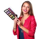 年轻美好的妇女举行在一只手和一个调色板上有油漆的和阴影构成的,中间人刷子构成的 免版税图库摄影