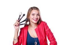年轻美好的妇女举行在一只手和一个调色板上有油漆的和阴影构成的,中间人刷子构成的 免版税库存照片