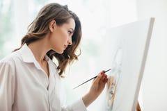 年轻美好的妇女绘画特写镜头在帆布的在演播室 免版税库存图片