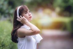 年轻美好的妇女身分和听到音乐在joggin以后 库存图片