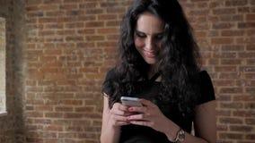 年轻美好的深色的女孩读书消息,微笑,通信概念,砖backgroung 影视素材