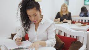 年轻美好的深色的计划她的在笔记本的天和放松在咖啡馆 股票视频