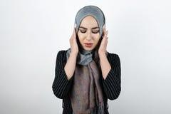 年轻美好的被激怒的回教妇女佩带的头巾hijab,看起来的头巾恼怒用她的关闭耳朵的手 库存图片