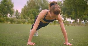 年轻美好的运动的健身女孩身分特写镜头画象在板条的在公园在户外都市城市 股票录像