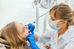年轻职业妇女牙医与患者一起使用 免版税图库摄影