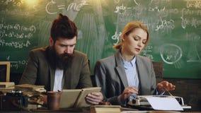年轻聪明的人民努力工作 男人和妇女学校课程的 人在打字机读书和妇女印刷品 ? 股票视频