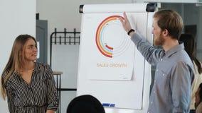 年轻聪明的欧洲企业教练专家的人主导的办公室研讨会,提出销售在flipchart用图解法表示 股票视频