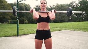 年轻肌肉妇女做着与杠铃的锻炼 股票视频