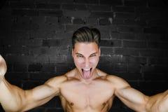 年轻肌肉爱好健美者健身式样摆在反对砖墙顶楼健身俱乐部 秀丽圆环闪光 图库摄影