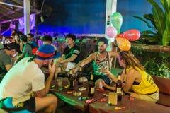 年轻背包徒步旅行者获得乐趣在其中一个酒吧中在Vang Vieng,老挝 免版税库存照片
