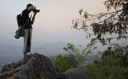 年轻背包徒步旅行者,在日落,琅勃拉邦小山顶的旅客照相 库存照片